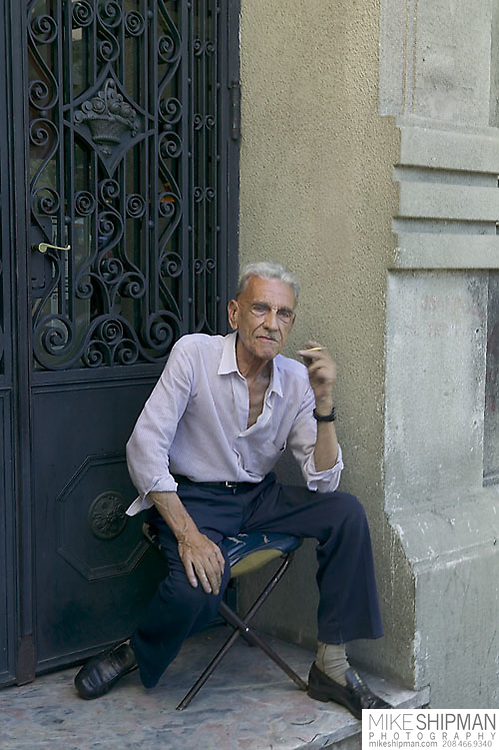 South America, Uruguay, Canelones, Montevideo, downtown, an elderly man wearing a button shirt, smoking, and sitting on a stool in an ornate doorway on Avenida 18 de Julio, the main street.