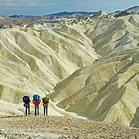 Hikers admire eroded sediments at Zabriskie Point, Death Valley National Park, California.