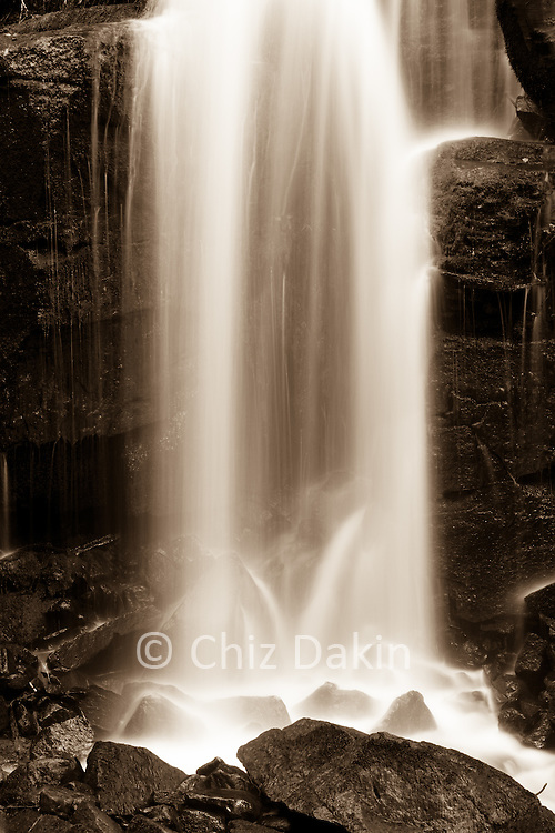 Sepia-toned image of water flowing over rocks at Lumsdale waterfall, Derbyshire