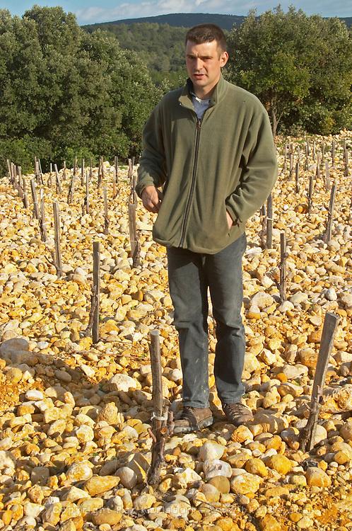Frédéric Pourtalié Domaine de Montcalmes in Puechabon. Terrasses de Larzac in vineyard of Dom Saint Sylvestre. Languedoc. Young Mourvedre grape vine variety. Terroir soil. Owner winemaker. France. Europe. Vineyard. Soil with stones rocks. Galets.