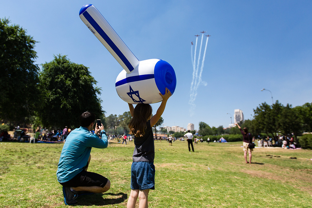 People watch as Israeli Air Force Aerobatic Team fly over Sacher Park in Jerusalem during Israel's 67th Independence Day, on May 12, 2016. Israel is celebrating its annual Independence Day, marking 68 years since the creation of the Jewish state.