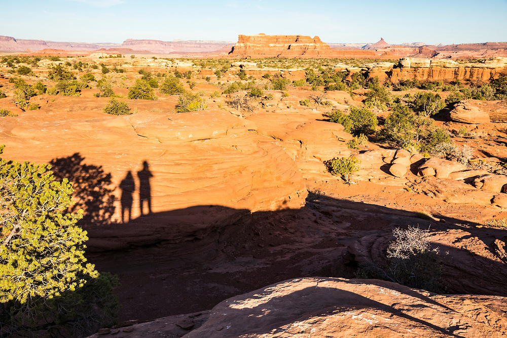 A photographer and companions shadows appear on a rock within his photograph of the landscape in Canyonlands National Park, Utah (The Needles District).
