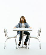 Out of focus woman in casual clothes sitting and thinking at table on white set with empty chairs