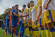 The mascot and Ian Henderson shake hands with the Gillingham players during the EFL Sky Bet League 1 match between Rochdale and Gillingham at Spotland, Rochdale, England on 15 September 2018.