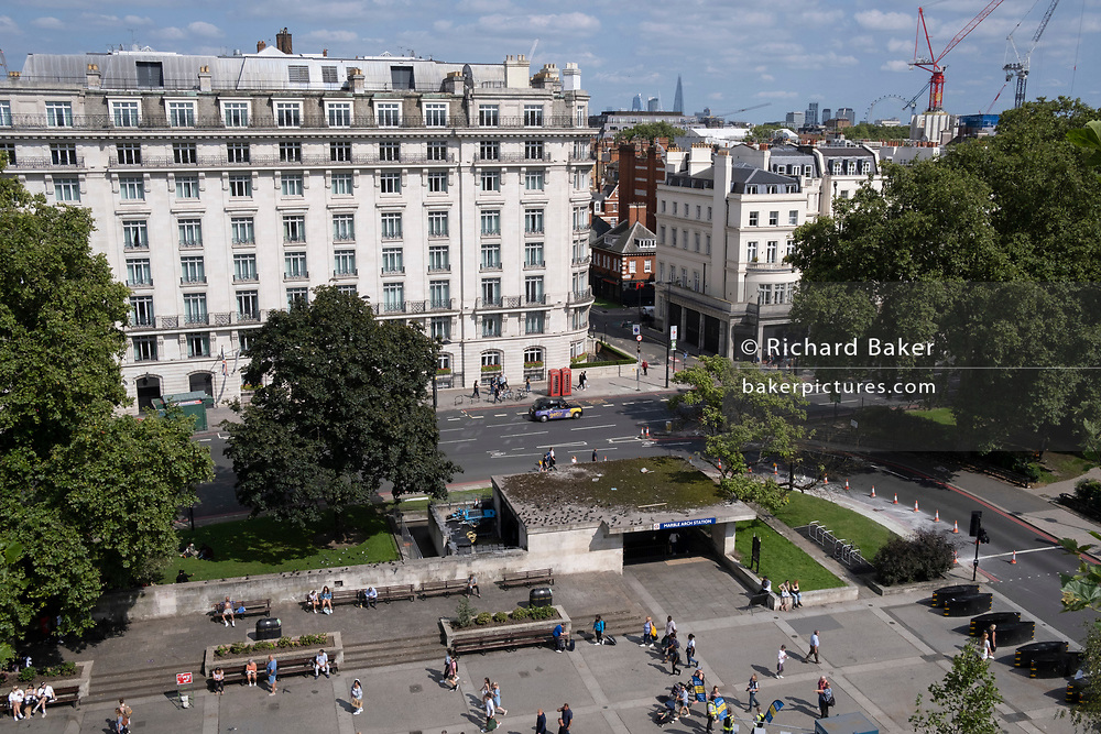 Seen from the elevation from the Marble Arch Mound is one entrance of Marble Arch tube station and the northern end of Park Lane, on 11th August 2021, in London, England.