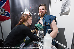 A member of the Irish Luck MC gets a tattoo in the Custom and Tuning Show, the custom bike show portion of the big Motor Spring bike show in Moscow, Russia. Sunday April 23, 2017. Photography ©2017 Michael Lichter.
