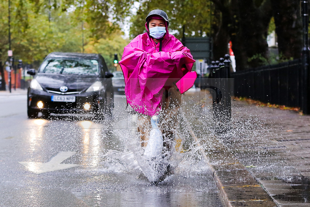 © Licensed to London News Pictures. 04/10/2020. London, UK. A woman wearing a face mask and raincoat rides her electric scooter through surface rainwater in north London, as Storm Alex brings heavy rain to large parts of the UK. The Met Office forecasts heavy rain and windy weather for the next of the day in the capital. Photo credit: Dinendra Haria/LNP
