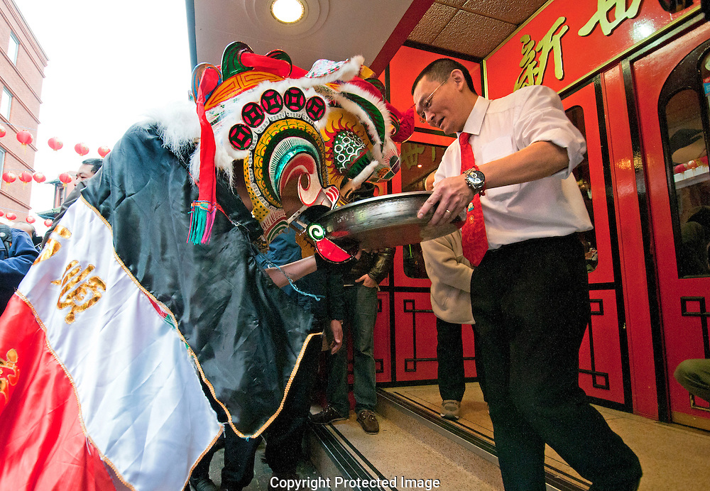 Chinese New Year traditon where Lion puppet is fed food  containing red envelope with money ( symbolising good luck )  by restaurants