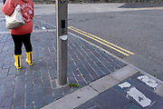 A pait of yellow boots and a street landscape of parallel and diagonal lines, on 7th October 2021, in Caernafon, Gwynedd, Wales.