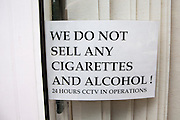 "Window sign stating: Wed no not sell any cigarettes and alcohol! 24 hours CCTV in operation""."