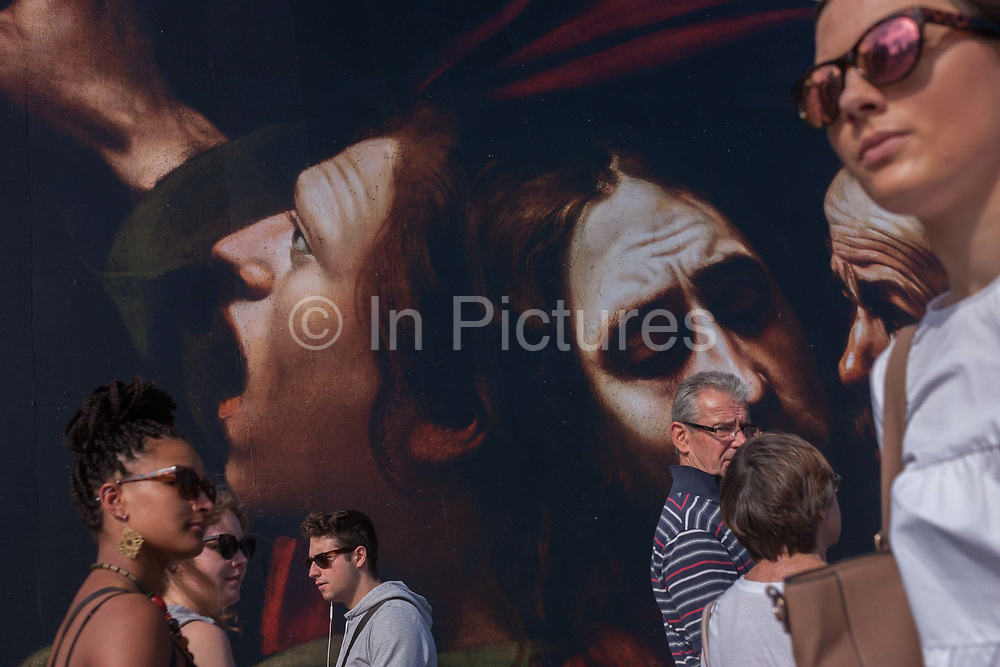 Visitors walk beneath the faces from The Taking of Christ c1602 the painting of the arrest of Jesus, by Italian Baroque master Caravaggio and currently being exhibited at the National Gallery, London.