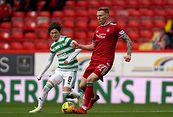 Celtic's Kyogo Furuhashi (left) and Aberdeen's David Bates in action during the cinch Premiership match at Pittodrie Stadium, Aberdeen. Picture date: Sunday October 3, 2021.