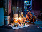 25 AUGUST 2018 - GEORGE TOWN, PENANG, MALAYSIA: A man sets up his family altar in front of his home on Ghost Day, the full moon day (or night) that falls in the middle of Hungry Ghost month. The Ghost Festival, also known as the Hungry Ghost Festival is a traditional Taoist and Buddhist festival held in Chinese communities throughout Asia. Ghost Day, is on the 15th night of the seventh month (25 August in 2018). During Ghost Festival, the deceased are believed to visit the living. In many Chinese communities, there are Chinese operas and puppet shows and elaborate banquets are staged to appease the ghosts.      PHOTO BY JACK KURTZ