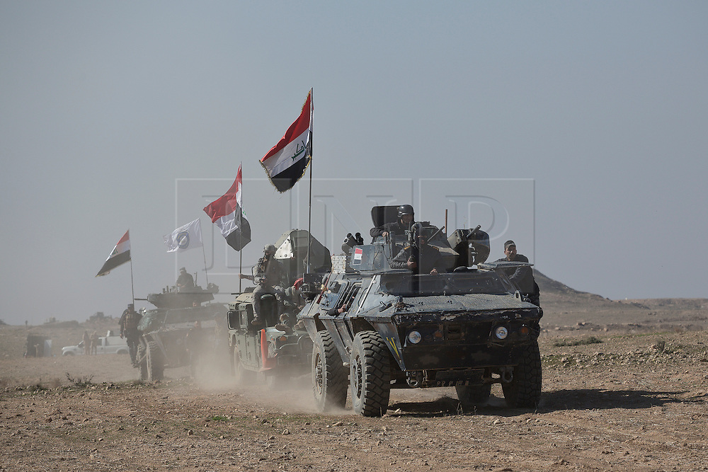 Licensed to London News Pictures. 20/02/2017. Albu Saif, Iraq. Iraqi Federal Police and Emergency Response Division soldiers advance towards Albu Saif as they take part in the offensive to retake western Mosul from the Islamic State.<br /> <br /> The settlement of Albu Saif is located on high ground overlooking Mosul Airport and as such is a strategic point that needs to be taken as part of the operation to retake the western side of Mosul. Photo credit: Matt Cetti-Roberts/LNP
