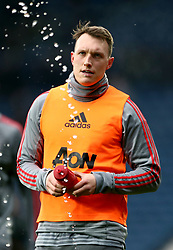 Manchester United's Phil Jones squirts his water bottle on the pitch during the pre-match warm up
