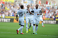Swansea city's Wayne Routledge (15) celebrates with Chico and Ashley Williams after  he scores his sides 1st goal. UEFA Europa league, play off round, 1st leg match, Swansea city v FC Petrolul Ploiesti at the Liberty stadium in Swansea on Thursday 22nd August 2013. pic by Andrew Orchard , Andrew Orchard sports photography,