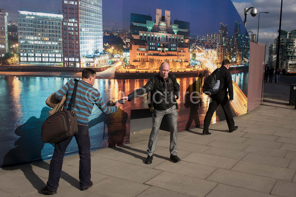 """A kind stranger retrieves a hat belonging to another pedestrian by a construction hoarding, a night time panorama of the Thames south bank, featuring the HQ of the intelligence service (MI6) across the river in Vauxhall. Under the gaze of a CCTV camera, the man hands over the item to its owner and  exchange thanks and expressions of gratitude. The temporary hoarding will stay in place for the time that the company's new residential riverfront apartments are under construction. In the image, the building at Vauxhall Cross, is located at 85 Albert Embankment beside Vauxhall Bridge. It is known within the intelligence community as """"Legoland"""" and """"Babylon-on-Thames""""."""