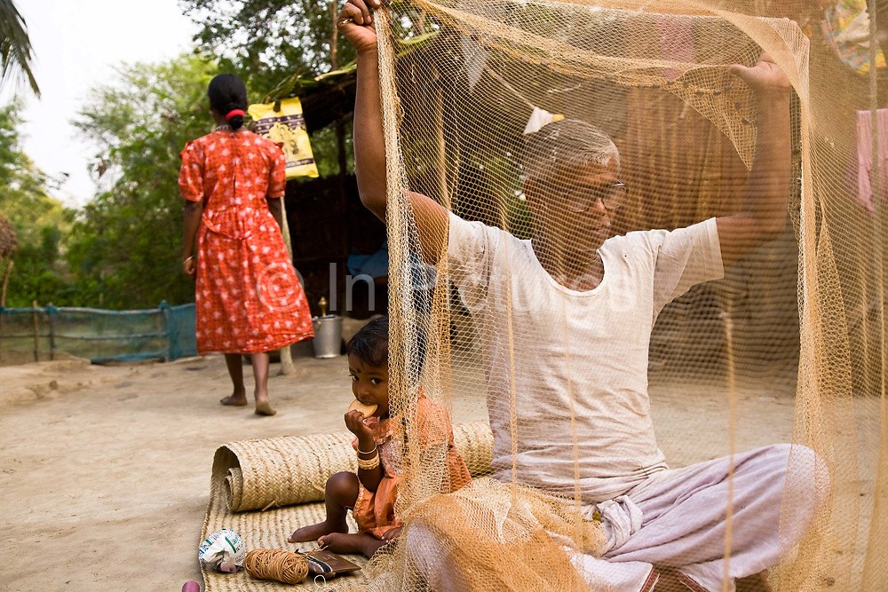 Monindro Mondol sits in the front yard of his village home repairing his fishing nets in the Sundrbans delta, West Bengal, India.
