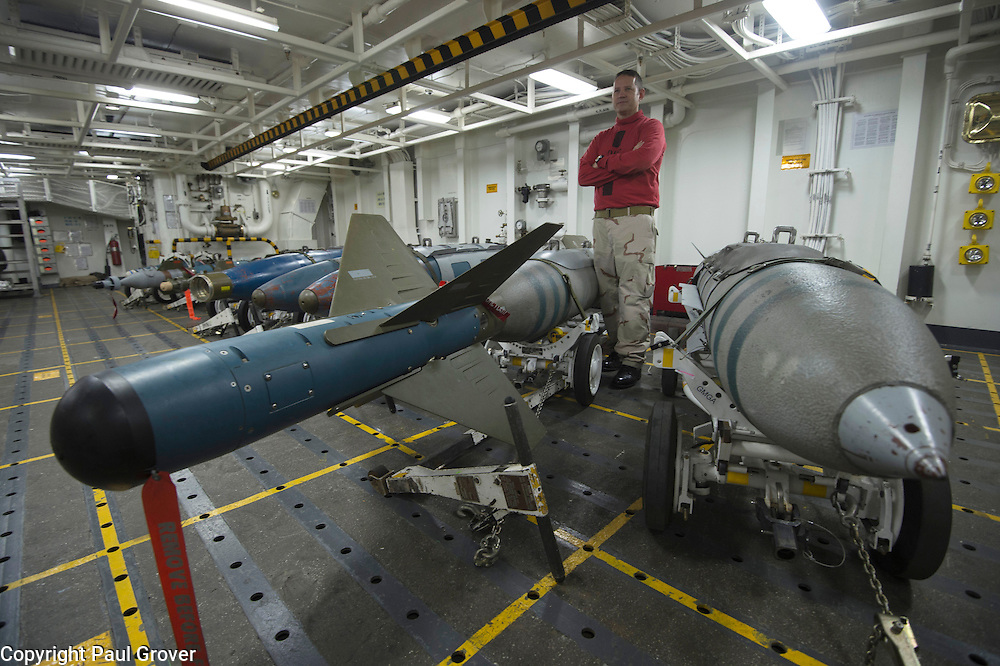 USS John C Stennis CVN-74 Aircraft Carrier.Pic Shows Ordnance Handling Officer William Donals with some of the weapons on the ship
