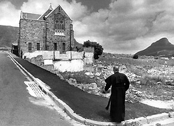 CA040708122<br /> CA/District 6. Cape Town. South Africa. 27 October 1983 - The rector of ST Marks, Reverend Stanley Gray stands before his church in the brick strewn landscape of District 6 (D6)<br /> ©Cape Argus/Trace Images   NO ARKS   NO SALES  CREDIT MANDATORY  NO ELECTRONIC RIGHTS