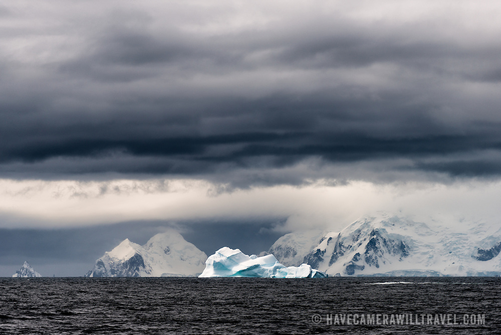 A blue iceberg floats by the rugged mountains of the northern Antarctic Peninsula, with dark clouds overhead.