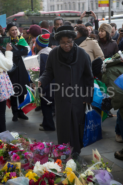 London, UK 6th December 2013: People gather near to the South African Embassy to lay flowers and pay tribute to former South African leader and anti-apartheid ANC campaigner Nelson Mandela, who died aged 95 on 5th December 2013.