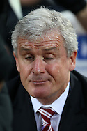 Mark Hughes, the Stoke City manager sits in the dugout before k/o. Barclays Premier league match, West Ham Utd v Stoke city at the Boleyn Ground, Upton Park  in London on Saturday 12th December 2015.<br /> pic by John Patrick Fletcher, Andrew Orchard sports photography.