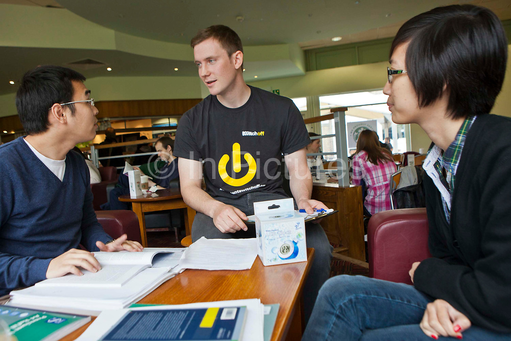 A young man from Student Switch Off performs a questionnaire about saving energy in the students union. The organisation encourages students to take simple steps to reduce their carbon footprint.