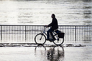 flood of the Rhine on February 4th, 2021, man rides a bicycle through the water on the flooded bank of the Rhine in Deutz, Cologne, Germany.<br /> <br /> Hochwasser des Rheins am 4. Februar 2021, Mann faehrt mit Fahrrad durch das Wasser am ueberfluteten Rheinufer in Deutz, Koeln, Deutschland.