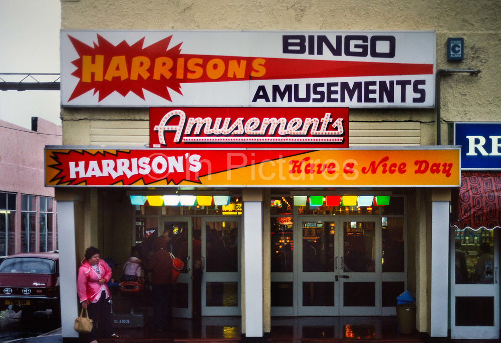 Harrisons amusements on a rainy day in Butlins holiday camp, Skegness. Butlins Skegness is a holiday camp located in Ingoldmells near Skegness in Lincolnshire. Sir William Butlin conceived of its creation based on his experiences at a Canadian summer camp in his youth and by observation of the actions of other holiday accommodation providers, both in seaside resort lodging houses and in earlier smaller holiday campsThe camp began opened in 1936, when it quickly proved to be a success with a need for expansion. The camp included dining and recreation facilities, such as dance halls and sports fields. Over the past 75 years the camp has seen continuous use and development, in the mid-1980s and again in the late 1990s being subject to substantial investment and redevelopment. In the late 1990s the site was re-branded as a holiday resort, and remains open today as one of three remaining Butlins resorts.