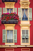 Typical French windows on residential building near the port in Nice, France.<br /> .....<br /> Nice is the fifth most populous city in France, after Paris, Marseille, Lyon and Toulouse, and it is the capital of the Alpes Maritimes département. The urban area of Nice extends beyond the administrative city limits with a population of about 1 million on an area of 278 sq mi. Located on the south east coast of France on the Mediterranean Sea, Nice is the second-largest French city on the Mediterranean coast and the second-largest city in the Provence-Alpes-Côte d'Azur region after Marseille.<br /> <br /> The city is called Nice la Belle, which means Nice the Beautiful, which is also the title of the unofficial anthem of Nice, written by Menica Rondelly in 1912. The area of today's Nice contains Terra Amata, an archaeological site which displays evidence of a very early use of fire. Around 350 BC, Greeks of Marseille founded a permanent settlement and called it Nikaia, after Nike, the goddess of victory. Through the ages, the town has changed hands many times. Its strategic location and port significantly contributed to its maritime strength. For years it was a dominion of Savoy, then became part of France between 1792 and 1815, when it was returned to Piedmont-Sardinia until its reannexation by France in 1860.<br /> <br /> The natural beauty of the Nice area and its mild Mediterranean climate came to the attention of the English upper classes in the second half of the 18th century, when an increasing number of aristocratic families took to spending their winter there. The city's main seaside promenade, the Promenade des Anglais ('the Walkway of the English') owes its name to the earliest visitors to the resort. For decades now, the picturesque Nicean surroundings have attracted not only those in search of relaxation, but also those seeking inspiration. The clear air and soft light has been of particular appeal to some of Western culture's most outstanding painters, suc