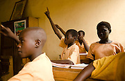 """Soale Ibrahim, 16, (center) attends class at the Nyologu Primary School in the village of Nyologu, northern Ghana, on Wednesday June 6, 2007. """"At school, we get egg, meat fish, that we usually don't eat at home,"""" says Soale..."""