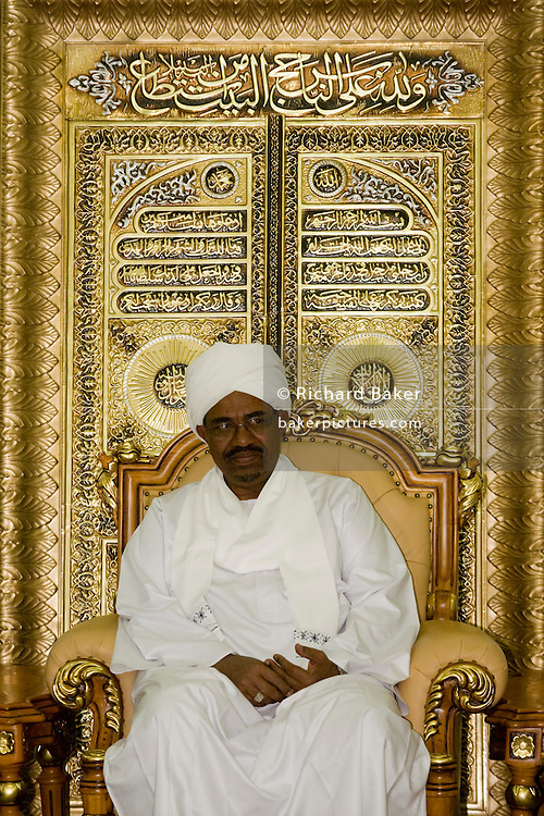 "Sudanese President, Omar Hassan Ahmad al-Bashir is seated against a gold leaf backdrop of Islamic texts in a reception room of his palace in central Khartoum. Al-Bashir is head of the National Congress Party and has been in power since October 1993. In 2009 he was indicted for war crimes by the ICC, (International Criminal Court) and represented as a bloodstained dictator by elements of the international media though is seemingly loved and respected for his role in empowering women. Secretary General of the National Council for Children's Welfare, Amira Elfadil, says ""He comes from within us all. He has a military background but he is a simple man, a man of the people, with good Islamic values. He speaks from his heart."""