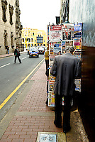 An old man chooses a magazine from a newspaper stand in Lima