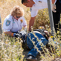 100213       Brian Leddy<br /> Gallup Med-Star personnel help a man who passed out on the side of the road Wednesday. The man was reportedly almost laying in traffic and was spotted by a New Mexico Department of Transportation employee.