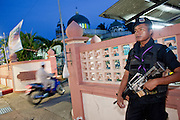 """Sept. 29, 2009 -- YARANG, THAILAND: A Thai Ranger provides security at a Mosque in Yarang as Muslims arrive for evening prayers. The Rangers are a paramilitary unit organized and led by the Thai army.  Thailand's three southern most provinces; Yala, Pattani and Narathiwat are often called """"restive"""" and a decades long Muslim insurgency has gained traction recently. Nearly 4,000 people have been killed since 2004. The three southern provinces are under emergency control and there are more than 60,000 Thai military, police and paramilitary militia forces trying to keep the peace battling insurgents who favor car bombs and assassination.   Photo by Jack Kurtz / ZUMA Press"""