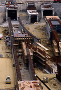 The new Channel Tunnel rail terminal under construction in the Kent countryside at Folkestone in 1989. A workman walks over part of the structure that will in the future, take the Eurostar and Shuttle trains through this portal underneath the town of Folkestone and on beneath the English Channel to the French coast. The technique is known as cut and cover. Eleven tunnel boring machines cut through chalk marl to construct two rail tunnels and a service tunnel. Tunnelling commenced in 1988, and the tunnel began operating in 1994. In 1985 prices, the total construction cost was £4.650 billion (equivalent to £11 billion today), an 80% cost overrun. At the peak of construction 15,000 people were employed with daily expenditure over £3 million. Ten workers were killed during construction between 1987 and 1993, most in the first few months of boring.