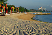 Section of Sanur Beach at sunrise, showing where beach has been raked clean. Sanur, Bali, Indonesia.