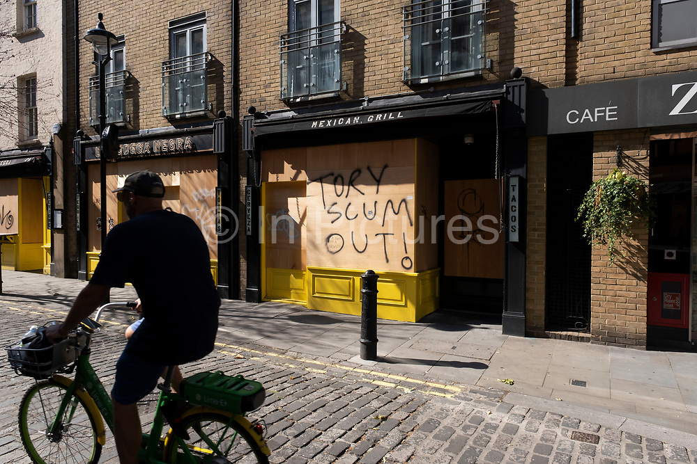 As the Coronavirus lockdown measures are set to ease further, and the quiet city starts coming to an end, some anti-Conservative party graffiti reading Tory Scum Out! on a boarded up restaurant in Soho on 25th June 2020 in London, England, United Kingdom. As the July deadline approaces and government will relax its lockdown rules further, the West End remains quiet, while some non-essential shops are allowed to open with individual shops setting up social distancing systems.