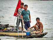 06 OCTOBER 2015 - BANGKOK, THAILAND:  Spotters on a salvage diver's boat on the Chao Phraya River in Bangkok. Divers work in two man teams on small boats in the Chao Phraya River. One person stays in the boat while the diver scours the river bottom for anything that can be salvaged and resold. The divers usually work close to shore because the center of the river is a busy commercial waterway with passenger boats and commercial freight barges passing up and down the river all day long. The Chao Phraya is a dangerous river to dive in. It's deep, has large tidal fluctuations, is fast flowing and badly polluted. The divers make money only when they sell something.    PHOTO BY JACK KURTZ