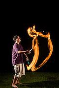 Boy juggling three flaming torches.