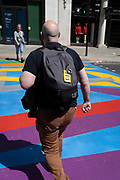 A man carrying a rucksack with a luggage label for international city destinations, walks over the multi-coloured markings of a crossing at Lower Regent Street, on 16th July 2021, in London, England.