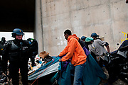 France , Calais, camp for refugees known as 'The Jungle'. September 21st 2015. French police oversee the removal of the tents and belongings in them, from under the flyover at the edge of the camp. This area was mainly populated by Eritreans.