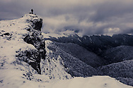 Man stays on a rock over a mountain gorge at gloomy winter weather