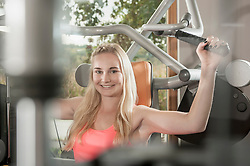 Attractive smiling blond woman fitness studio