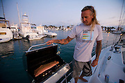 Surfer Ernie Johnson grills fish on his 38 foot sailboat moored at Dana Point Harbor in California. (Ernie Johnson is featured in the book What I Eat: Around the World in 80 Diets.) MODEL RELEASED.