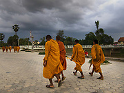 Young Buddhist monks are walking along the river in Battambang, it's evening and rush hour.
