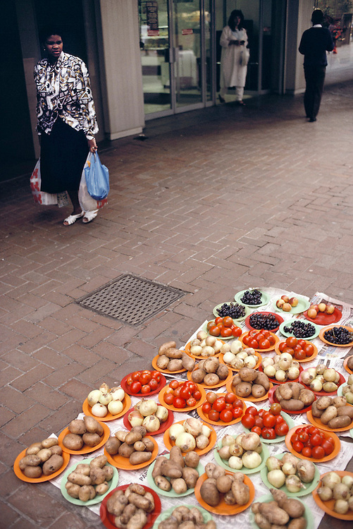 Poppy Qampie passes by root vegetables and fruit for sale by the plate full near the office where she works as an assistant in downtown Johannesburg (Joberg), South Africa. The Qampie family lives in a 400 square foot concrete block duplex house in the sprawling area of Southwest Township (called Soweto), outside Johannesburg (Joberg) South Africa. Material World Project.