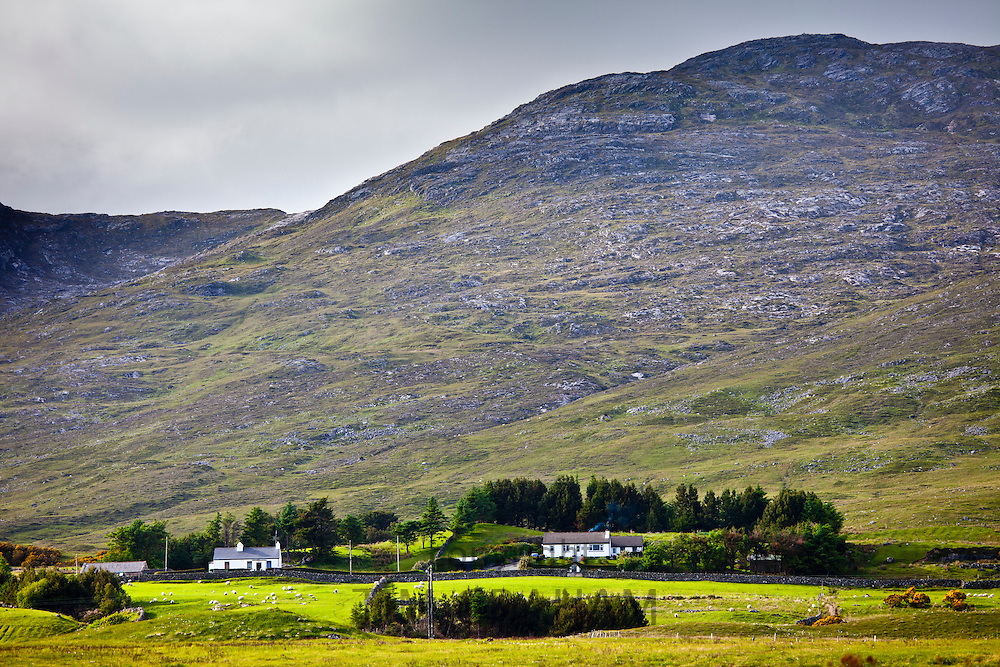 Homes nestling at the foot of the Maumturk Mountains near Recess, Connemara, County Galway, Ireland