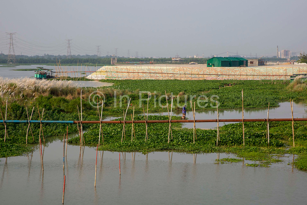A man walks across a raised pipe line next to the Turag river on the 30th of September 2018 in Dhaka, Bangladesh.